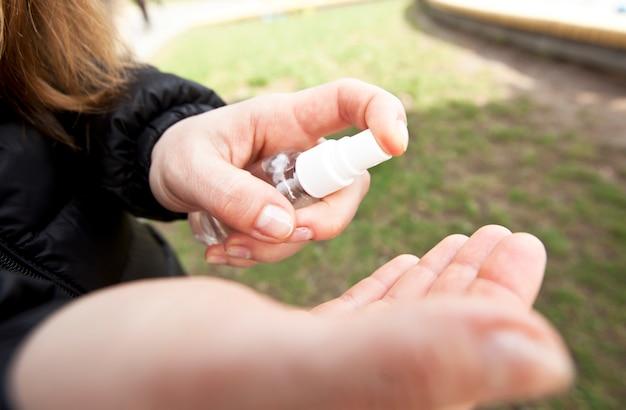 Młoda kobieta dezynfekuje rękę przez środek dezynfekujący