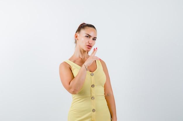 Młoda kobieta dmuchanie na palec pistolet w żółtej sukience i patrząc pewnie. przedni widok.