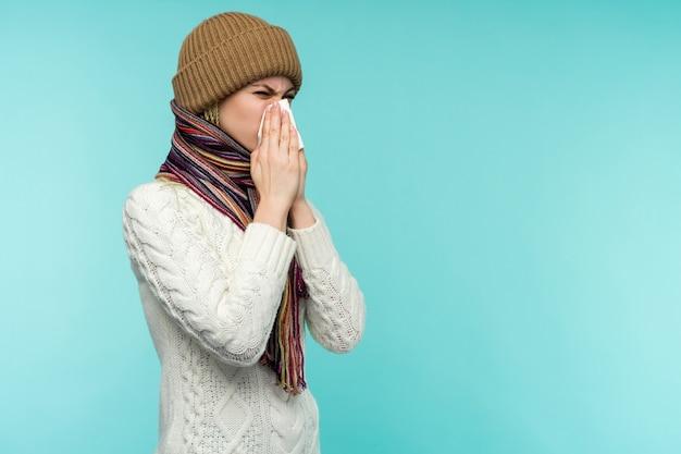 Młoda kobieta dmuchanie nosa w tkankę