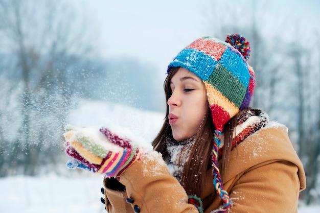 Młoda kobieta dmuchanie śniegu daleko