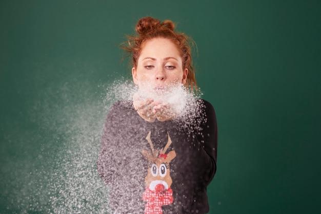 Młoda kobieta dmuchanie sztuczny śnieg