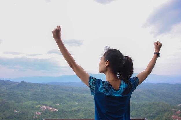 Młoda kobieta doping z otwartymi ramionami na szczyt