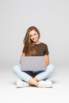 Młoda Kobieta Dorywczo Siedzi Uśmiechnięty Trzymając Laptop Na Białym Tle Na Białej ścianie Darmowe Zdjęcia