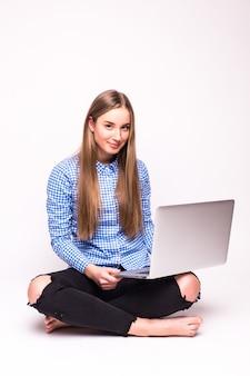 Młoda kobieta dorywczo siedzi uśmiechnięty trzymając laptop na białym tle na białej ścianie