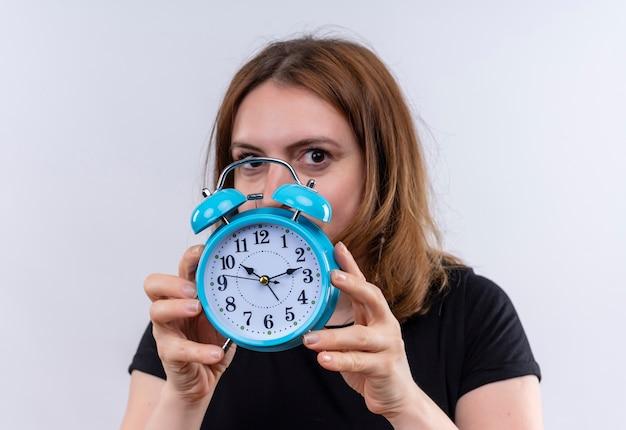 Młoda kobieta dorywczo trzymając budzik i chowając się za nim na odosobnionej białej ścianie