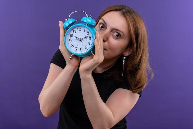 Młoda kobieta dorywczo trzymając budzik i chowając się za nim patrząc na odosobnioną fioletową ścianę