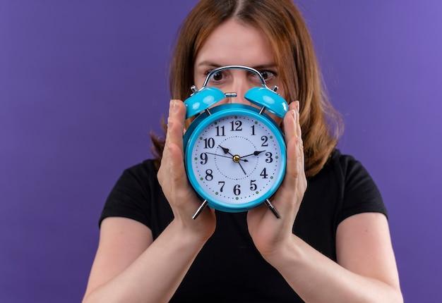 Młoda kobieta dorywczo trzymając i chowając się za budzikiem i patrząc na to na odosobnionej fioletowej ścianie