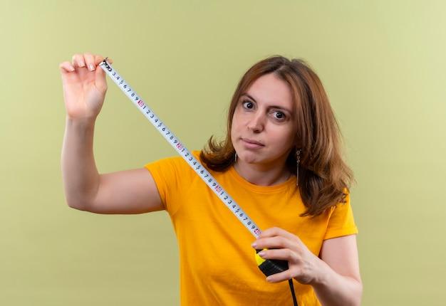 Młoda kobieta dorywczo trzymając miernik taśmy i na odosobnionej zielonej ścianie