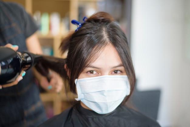 Młoda kobieta dostaje fryzurę w salonie fryzjerskim, ubrana w maskę na twarz covid-19, koncepcja bezpieczeństwa w salonie