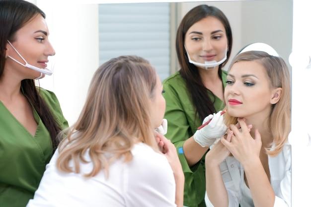 Młoda kobieta dostaje makijaż. tatuaż na ustach w salonie kosmetycznym.