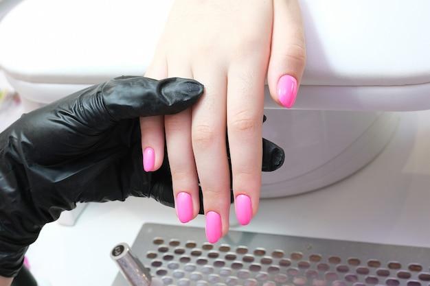Młoda kobieta dostaje manicure w salonie. nakładanie szelaku na paznokcie. kolor różowy