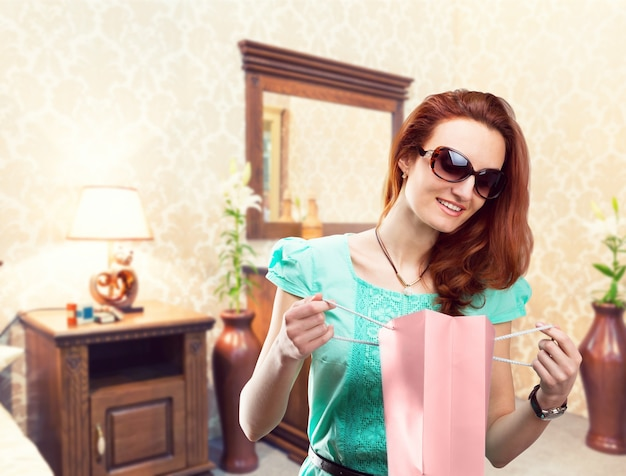 Młoda kobieta dostaje prezent z torby na zakupy w domu