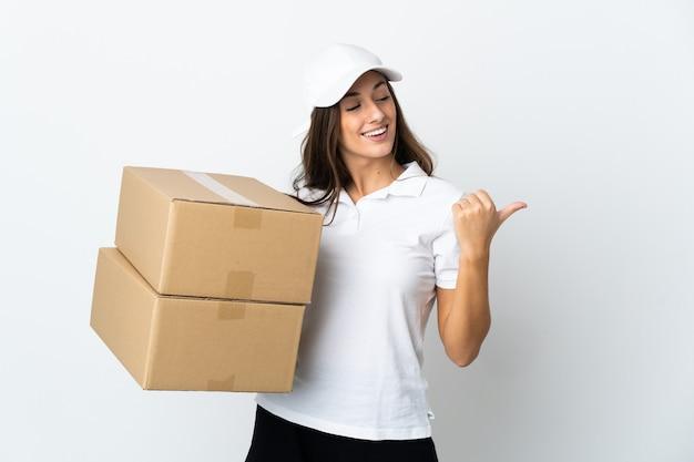 Młoda kobieta dostarczająca na białym tle, wskazując na bok, aby zaprezentować produkt