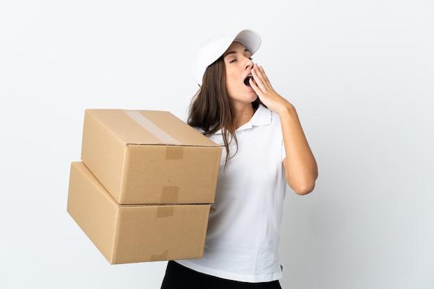 Młoda kobieta dostarczająca na białym tle ziewa i zakrywa ręką szeroko otwarte usta