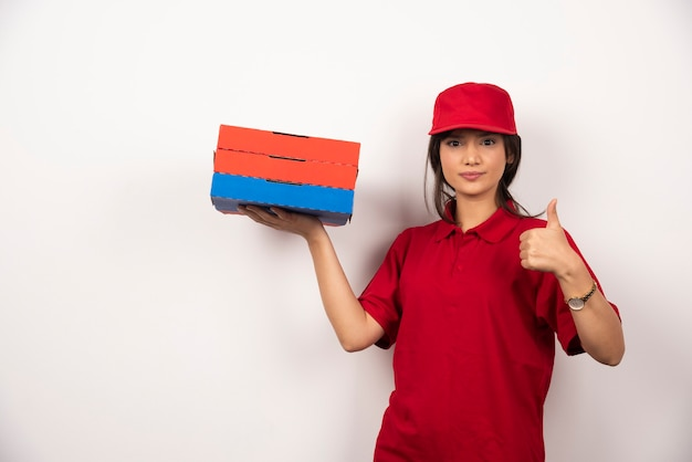 Młoda kobieta dostawa pizzy pracownik stojący z trzema kartonami pizzy.
