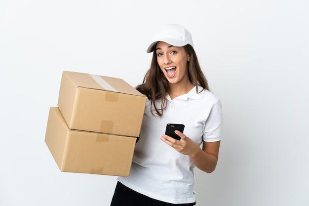 Młoda kobieta dostawcza na białym tle zaskoczona i wysyłająca wiadomość