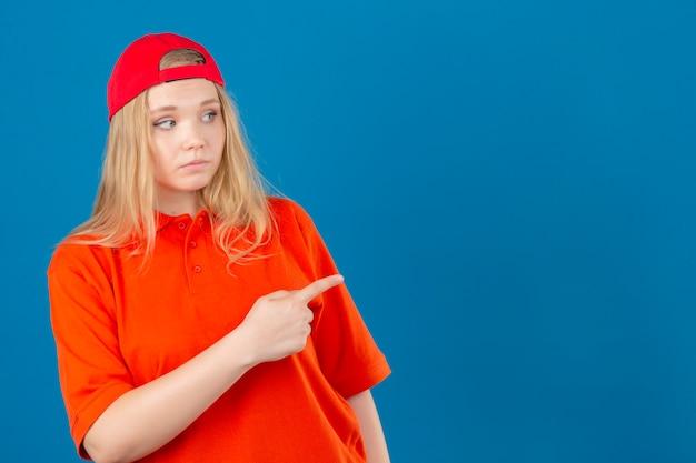 Młoda kobieta dostawy ma na sobie pomarańczową koszulkę polo i czerwoną czapkę patrząc na bok, wskazując palcem wskazującym na przestrzeń kopii na pojedyncze niebieskie tło