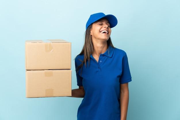 Młoda kobieta dostawy na białym tle na niebieskim tle śmiechu