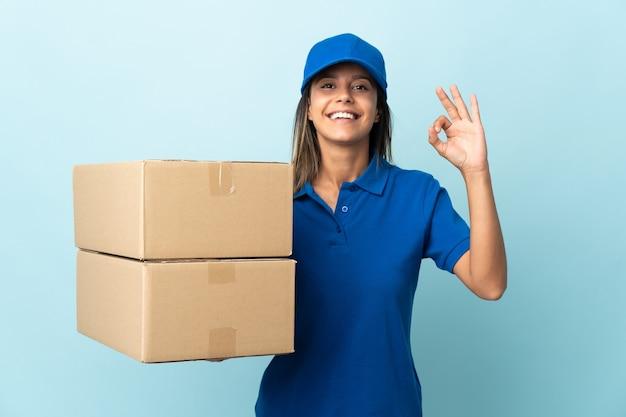 Młoda kobieta dostawy na białym tle niebieski wyświetlono znak ok palcami