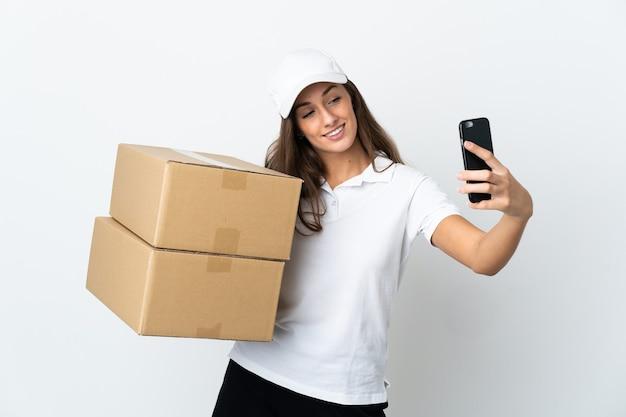 Młoda kobieta dostawy na białym tle robi selfie