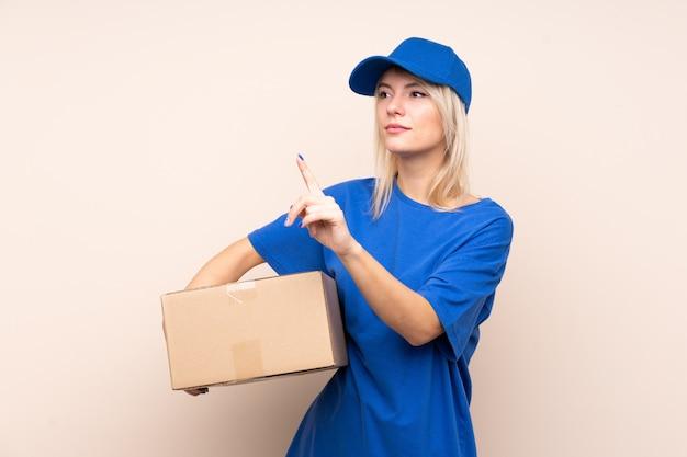 Młoda kobieta dostawy na białym tle ściany dotykając przejrzysty ekran