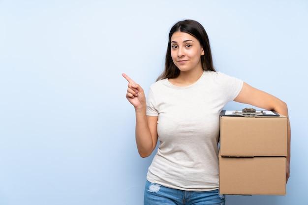 Młoda kobieta dostawy na niebieskim murem, wskazując na bok, aby przedstawić produkt