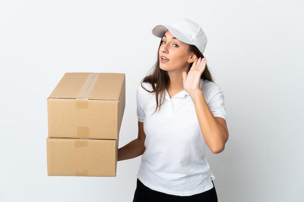 Młoda kobieta dostawy na pojedyncze białe ściany słuchając czegoś, kładąc rękę na uchu