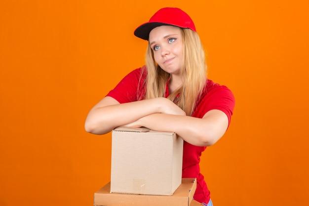 Młoda kobieta dostawy na sobie czerwoną koszulkę polo i czapkę czeka ze skrzyżowaną ręką na stosie pudeł kartonowych, patrząc zmęczony i chory na pojedyncze pomarańczowe tło