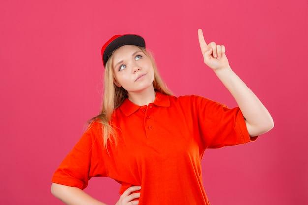 Młoda kobieta dostawy na sobie czerwoną koszulkę polo i czapkę patrząc w górę i wskazując na coś palcem wskazującym na na białym tle różowym tle