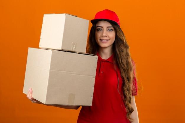 Młoda kobieta dostawy na sobie czerwoną koszulkę polo i czapkę stojącą z kartonami, patrząc pewnie na pojedyncze pomarańczowe tło