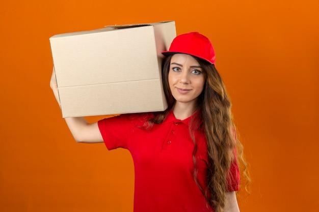 Młoda kobieta dostawy na sobie czerwoną koszulkę polo i czapkę stojącą z tekturowym pudełkiem na ramieniu, patrząc pewnie na pojedyncze pomarańczowe tło