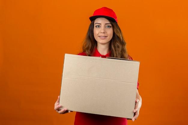 Młoda kobieta dostawy na sobie czerwoną koszulkę polo i czapkę stojącą z tekturowym pudełkiem patrząc pewnie na pojedyncze pomarańczowe tło