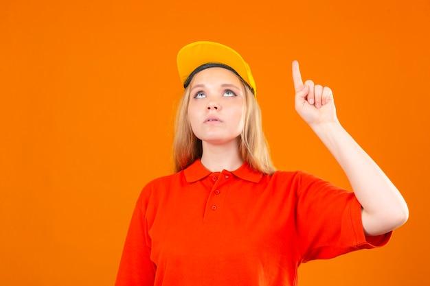 Młoda kobieta dostawy na sobie czerwoną koszulkę polo i żółtą czapkę patrząc w górę i wskazując palcem wskazującym na na białym tle pomarańczowym tle