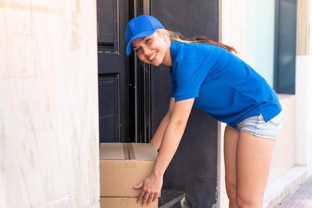 Młoda kobieta dostawy na zewnątrz, pozostawiając pudełka przy drzwiach
