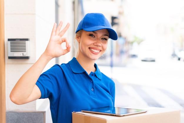 Młoda kobieta dostawy na zewnątrz, trzymając pudełka i tablet i robiąc znak ok
