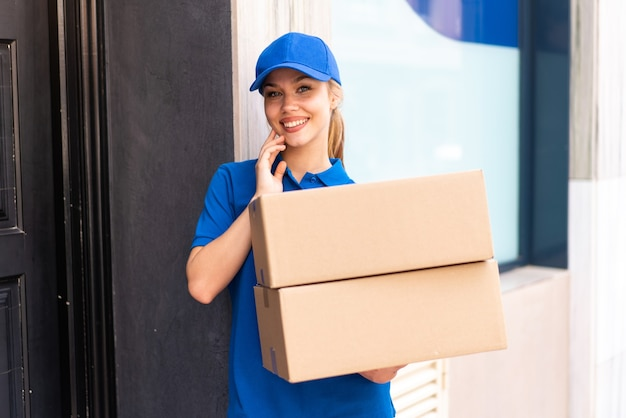 Młoda kobieta dostawy na zewnątrz, trzymając pudełka ze szczęśliwym wyrazem twarzy