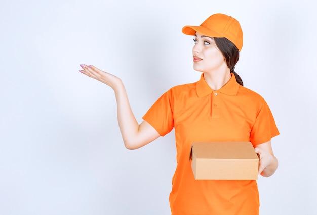 Młoda kobieta dostawy trzymająca rękę w górze i patrząca na nią