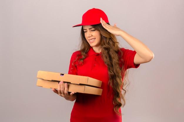 Młoda kobieta dostawy ubrana w czerwoną koszulkę polo i czapkę patrząc źle dotykając głowy cierpiących na bóle głowy na na białym tle