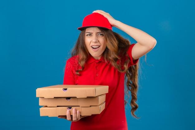 Młoda kobieta dostawy ubrana w czerwoną koszulkę polo i czapkę stojącą z pudełkami po pizzy zszokowana ręką na głowie za błąd pamięta błąd zapomniał złej koncepcji pamięci na izolowanym białym tle