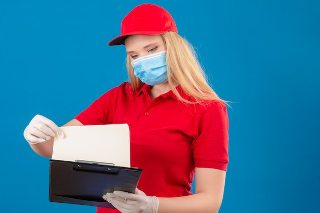 Młoda kobieta dostawy ubrana w czerwoną koszulkę polo i czapkę w medycznej masce ochronnej patrząc na schowek w rękach z poważną twarzą skoncentrowaną na zadaniu na odosobnionym niebieskim tle