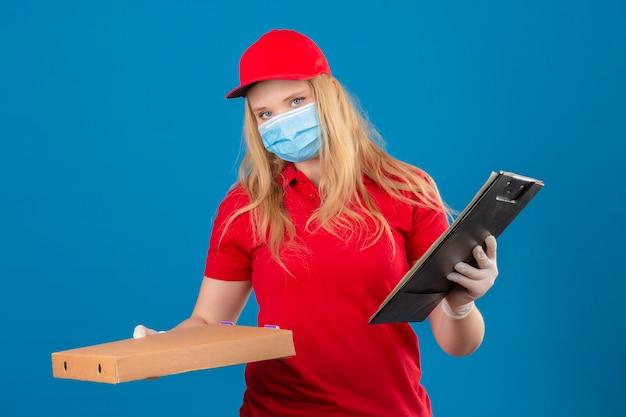Młoda kobieta dostawy ubrana w czerwoną koszulkę polo i czapkę w medycznej masce ochronnej stojącej z pudełkiem po pizzy i schowkiem patrząc na kamerę z poważną twarzą na białym tle