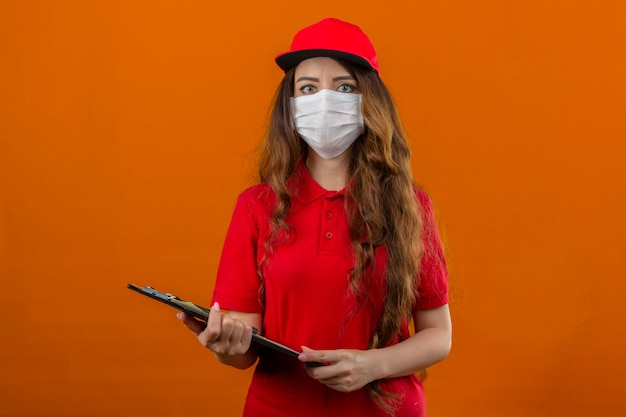 Młoda kobieta dostawy ubrana w czerwoną koszulkę polo i czapkę w medycznej masce ochronnej stojącej ze schowkiem patrząc na kamerę z poważną twarzą na odizolowanym pomarańczowym tle