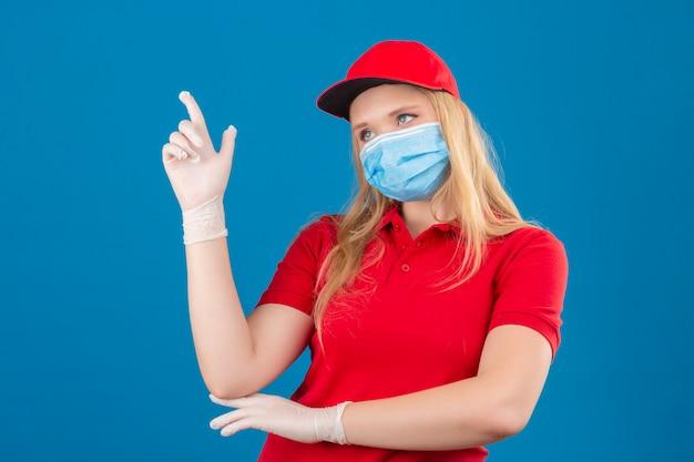 Młoda kobieta dostawy ubrana w czerwoną koszulkę polo i czapkę w medycznej masce ochronnej, wskazując palcem wskazującym na świetny pomysł na odosobnionym niebieskim tle