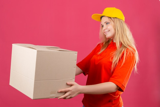 Młoda kobieta dostawy ubrana w czerwoną koszulkę polo i żółtą czapkę, dając klientowi karton z uśmiechem na twarzy na na białym tle różowym tle