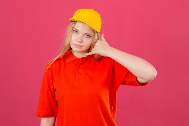 Młoda kobieta dostawy ubrana w czerwoną koszulkę polo i żółtą czapkę, która sprawia, że zadzwoń do mnie gest patrząc pewnie na na białym tle różowym