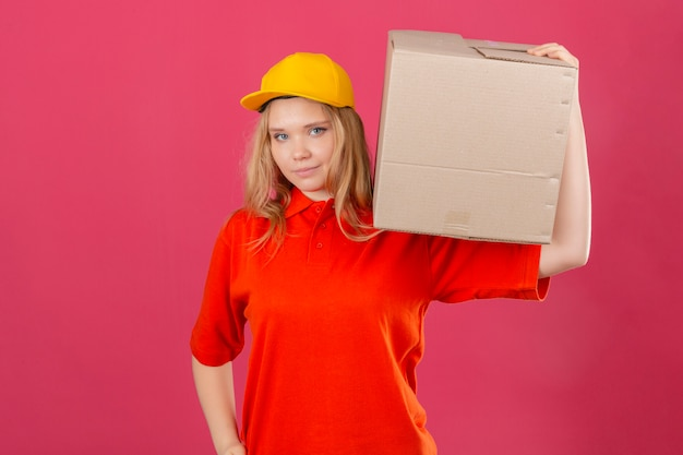 Młoda kobieta dostawy ubrana w czerwoną koszulkę polo i żółtą czapkę stojącą z tekturowym pudełkiem na ramieniu, patrząc pewnie na pojedyncze różowe tło