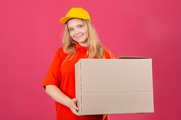 Młoda kobieta dostawy ubrana w czerwoną koszulkę polo i żółtą czapkę, trzymając duży karton uśmiechnięty przyjazny z radosną buźką na odosobnionym różowym tle