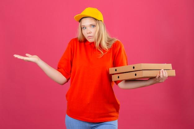 Młoda kobieta dostawy ubrana w czerwoną koszulkę polo i żółtą czapkę, trzymając pudełka po pizzy, wzruszając ramionami, patrząc zdezorientowany na odosobnionym różowym tle