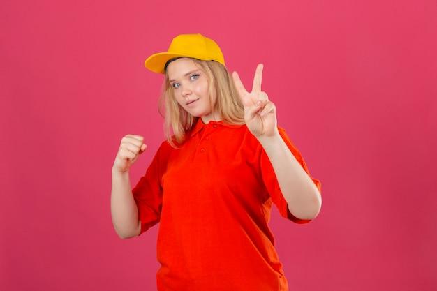 Młoda kobieta dostawy ubrana w czerwoną koszulkę polo i żółtą czapkę, uśmiechając się, podnosząc pięść i pokazując koncepcję zwycięzcy znak zwycięstwa na izolowanym różowym tle