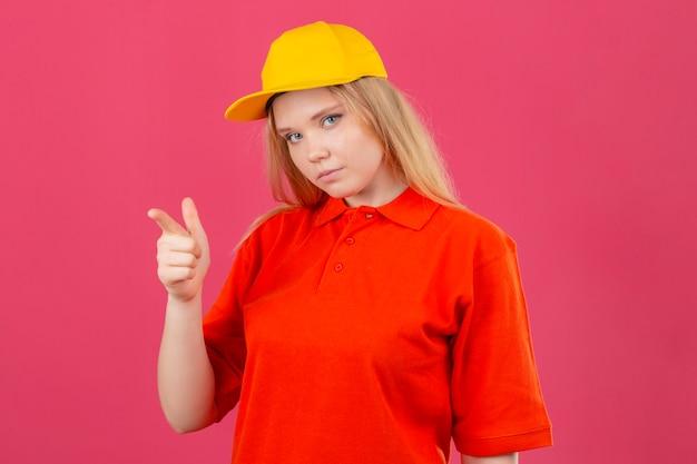 Młoda kobieta dostawy ubrana w czerwoną koszulkę polo i żółtą czapkę, wskazując palcem wskazującym w kierunku aparatu, patrząc pewnie na pojedyncze różowe tło